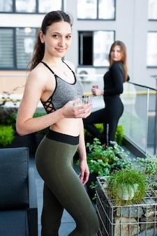 Le donne si rilassano e bevono in modo sano dopo la palestra