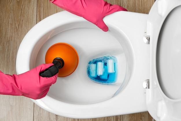 Donne che puliscono la toilette intasata. toilette straripante rotto. concetto di servizio di pulizia della casa.
