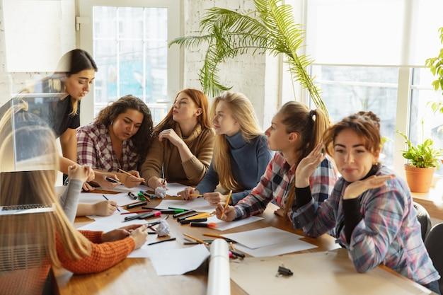 Donne che discutono e preparano poster sui diritti e l'uguaglianza delle donne in ufficio
