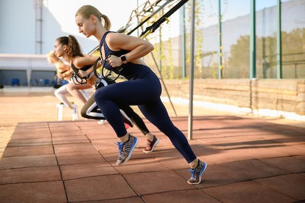 Donne che fanno esercizio di stretching sul campo sportivo all'aperto, allenamento fitness di gruppo all'esterno