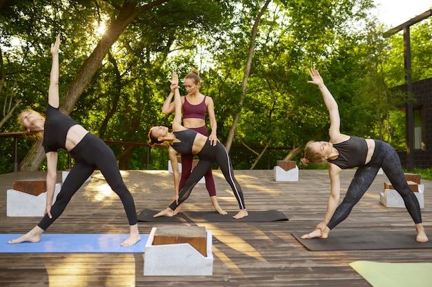 Donne che fanno esercizio di stretching con istruttore, formazione yoga di gruppo sull'erba nel parco. meditazione, lezione di allenamento all'aperto