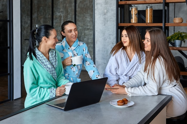 Le donne in vestaglia fanno colazione al tavolo della sala da pranzo e chiacchierano mentre sfogliano le notizie sui computer portatili