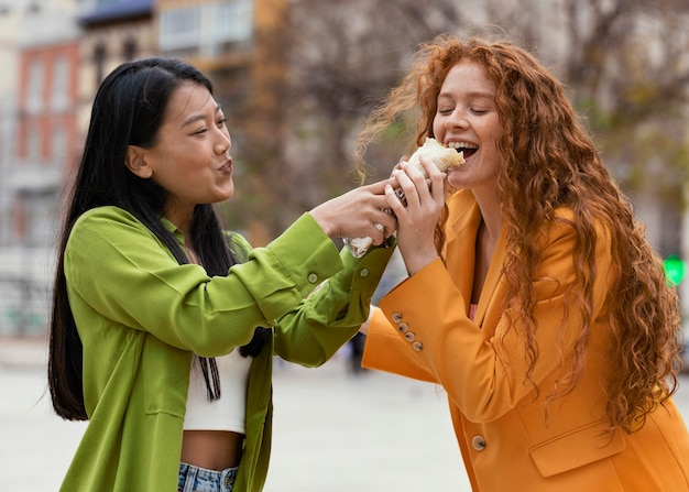 Donne che mangiano cibo di strada all'aperto