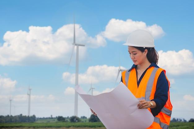 Ingegnere delle donne che lavora in loco presso la turbina eolica