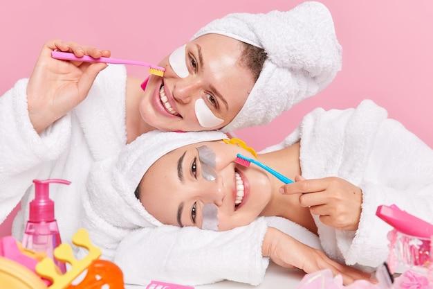 Le donne godono di procedure igieniche e di bellezza tenere gli spazzolini da denti applicare cerotti di bellezza sotto gli occhi vestiti con abiti domestici isolati su rosa