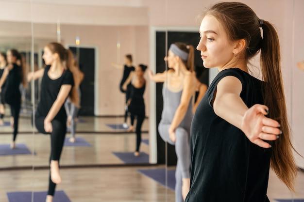 Donne che esercitano in lezioni di yoga studio fitness, sport e concetto di salute