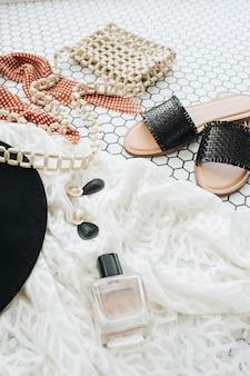 Accessori di moda delle donne sulle mattonelle di mosaico bianco. collage di stile di vita alla moda di blogger di moda. pantofole, cappello, borsetta, profumo, orecchini, occhiali da sole