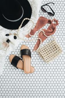 Accessori di moda delle donne sulle mattonelle di mosaico bianco. collage di stile di vita alla moda minimo vista dall'alto, piatto laico. pantofole, cappello, borsetta, profumo, orecchini, occhiali da sole