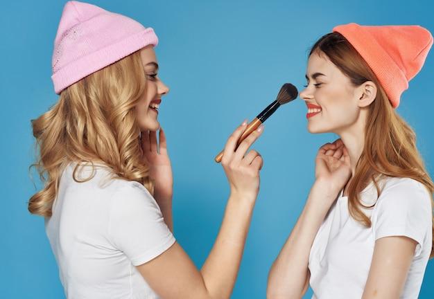 Donne in vestiti di moda divertimento di amicizia di cosmetici. foto di alta qualità