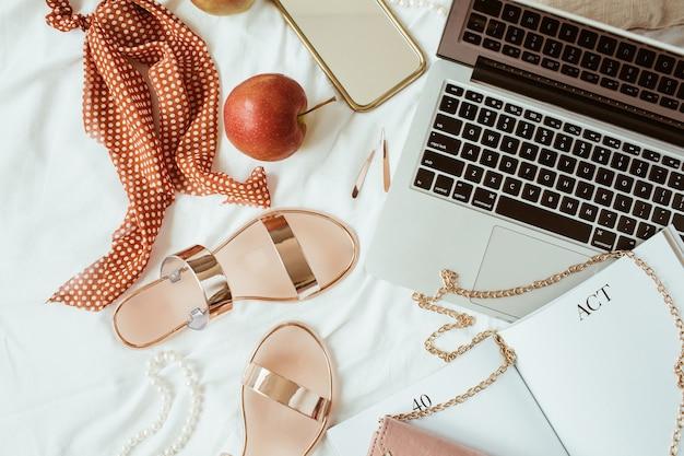 Spazio di lavoro a casa in stile rosa moda donna con bigiotteria e laptop su lino bianco