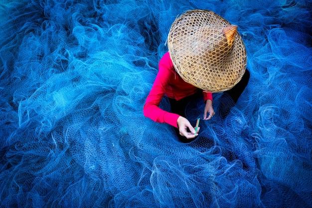 Le mani del pescatore delle donne cuciono le reti da pesca blu che si siedono sulla terra