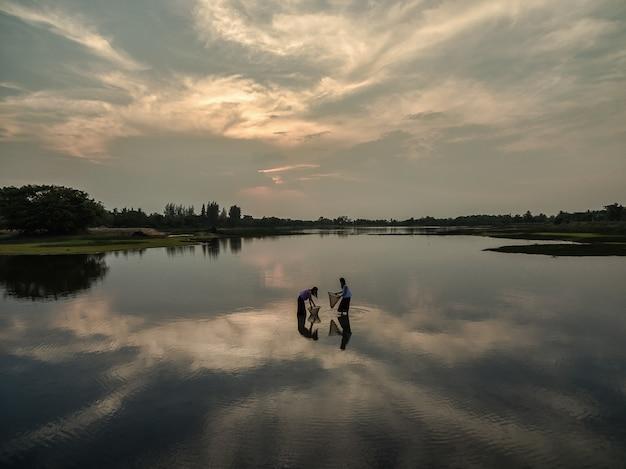 Donne che pescano al lago per il cibo