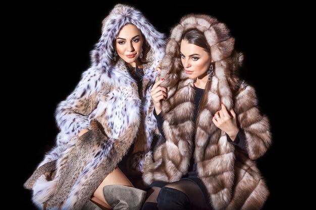 Donne in pelliccia due bellissime e giovani modelle in posa con le pellicce della lince e del visone