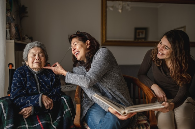 Generazione di donne con la vecchia nonna ammalata seduta in sedia a rotelle e sorridente figlia e nipote alla ricerca di un album fotografico.