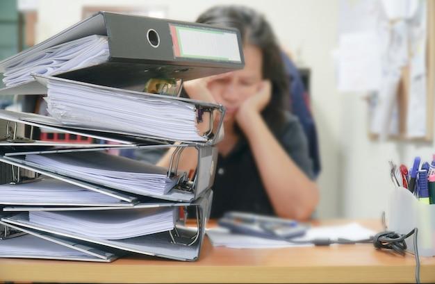 Le donne ottengono più lavoro con un sacco di duro lavoro con documenti impilati.