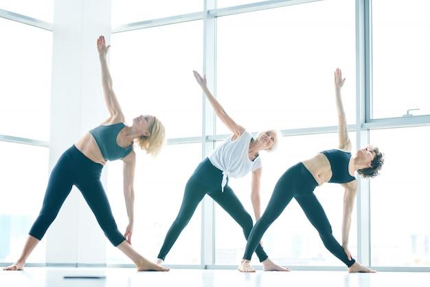 Gruppo di donne che fa yoga accanto a una grande finestra
