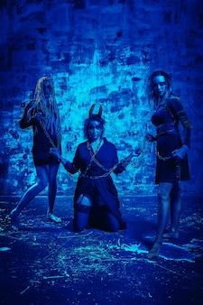 Donne in abito di halloween in posa con su sfondo blu. la splendida ragazza in abiti celebra il giorno dei morti. concetto di halloween, costume da strega, colori vivaci, filtro blu.