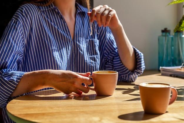 Mano delle donne e tazza di caffè sulla scrivania in legno nella caffetteria o caffetteria da vicino