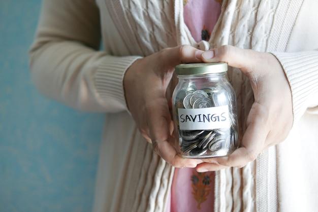 Le donne tengono in mano un barattolo di monete per risparmiare