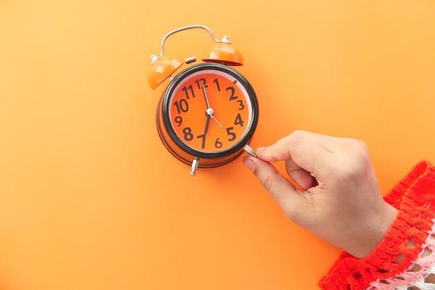 Mano delle donne che tiene la priorità bassa arancione della sveglia,