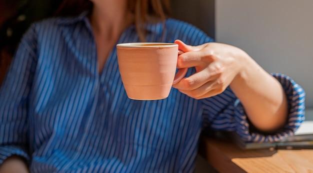 Mano delle donne che tiene la tazza di caffè da vicino e luce del giorno