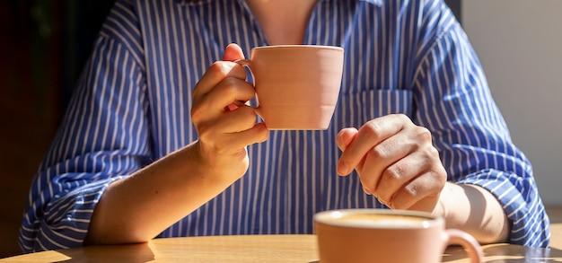 Mano delle donne che tiene la tazza di caffè sul tavolo di legno nella caffetteria in una giornata di sole con il primo piano della luce del giorno