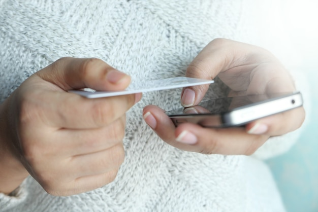 Mano delle donne che tiene la carta di credito e utilizzando smart phone acquisti online.