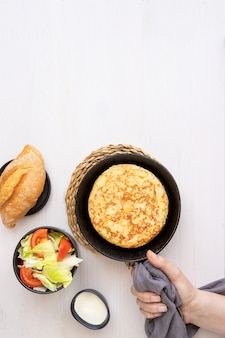 Mano delle donne che tiene la padella con tortilla, frittata spagnola fatta con uova e patate e servita con insalata e pane. vista dall'alto.