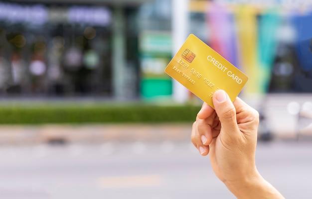 Mano delle donne che tiene la carta del membro della carta di credito dell'oro sopra il fondo del grande magazzino della sfuocatura. affari, shopping, concetto di stile di vita. con copia spazio