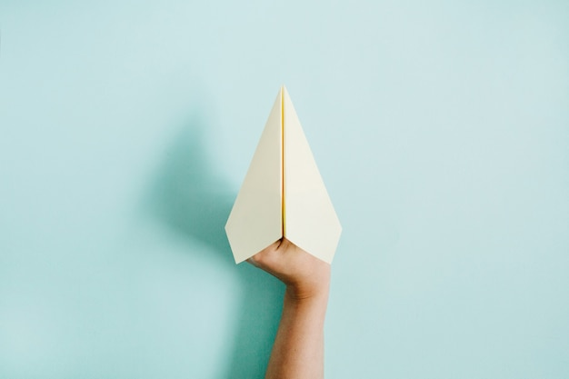 Mano delle donne che tiene l'aereo di carta sul blu pallido