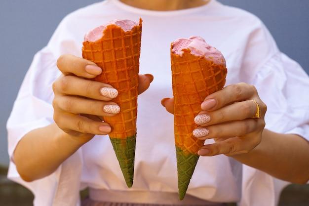 Mano delle donne che tiene cono gelato arcobaleno. cono gelato arcobaleno - due mani che tengono coni gelato nei colori dell'arcobaleno in una calda giornata estiva
