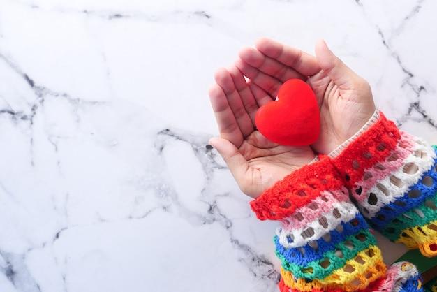 Mano delle donne che tiene il fondo rosso delle mattonelle del cuore con lo spazio della copia,