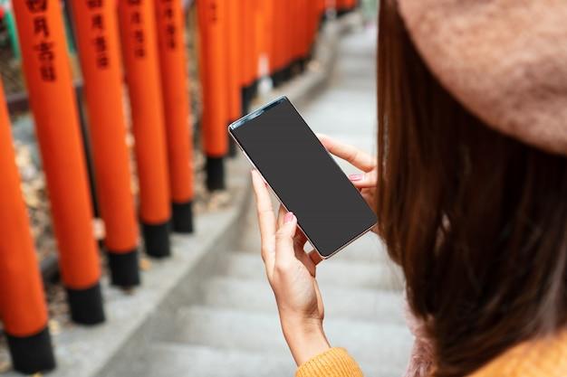 Smart phone della tenuta della mano delle donne con lo schermo in bianco