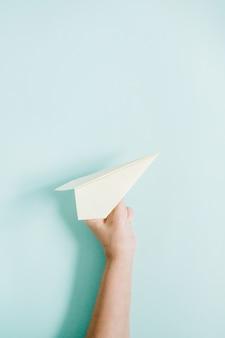 Mano delle donne che tiene l'aereo di carta bianco su blu pallido
