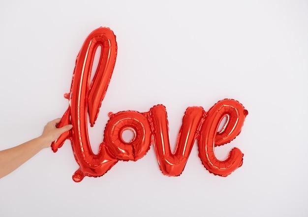 La mano delle donne tiene l'amore dell'iscrizione rossa dai palloncini su una parete bianca.