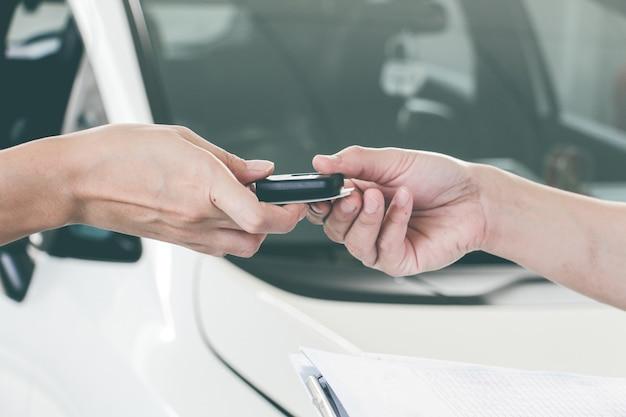 Mano delle donne e mano degli uomini che danno la chiave moderna dell'auto con lo sfondo dell'auto. concetto di trasporti. vendi o acquista un nuovo concetto di auto. concetto di manutenzione.
