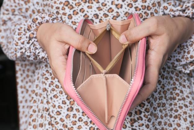 La mano delle donne apre un portafoglio vuoto in primo piano.