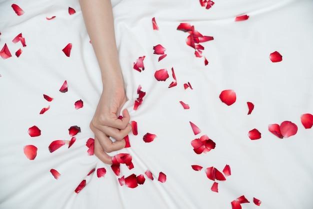 Le donne tirano o afferrano le lenzuola bianche. segno della mano orgasmo della donna sul lenzuolo bianco con petali di rosa.