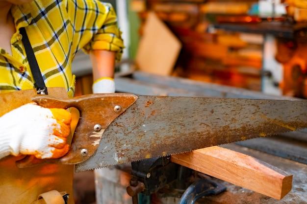La mano delle donne sta segando la tavola di legno su fondo sbavato