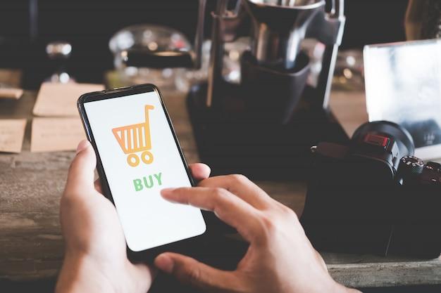 Le donne passano con lo smartphone facendo affari online o facendo acquisti online nel venerdì nero con il carrello, pop-up di icone del dollaro nell'area pubblica
