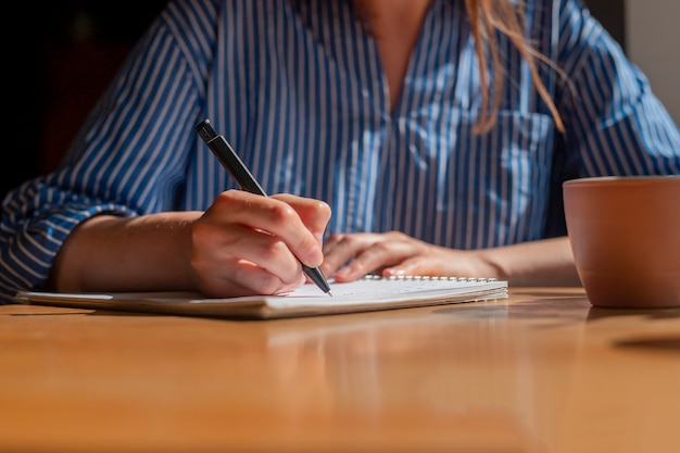 Le donne passano con la penna scrivendo piani nel pianificatore o prendendo appunti sul taccuino sul primo piano del tavolo di legno