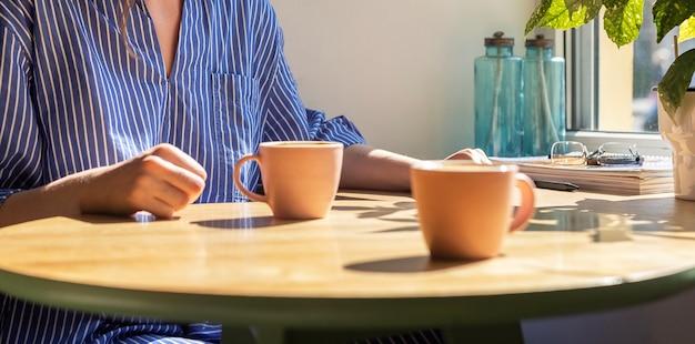 Le mani delle donne al bar all'incontro con le tazze di caffè smb sulla luce del sole del tavolo