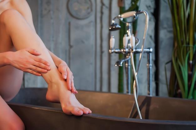 Le mani delle donne fanno un massaggio ai piedi con olio cosmetico per applicare gocce sulla pelle durante il bagno. la femmina applica l'olio sullo sfondo di un vecchio bagno interno. concetto di stile di vita sano e cura di sé. copia spazio
