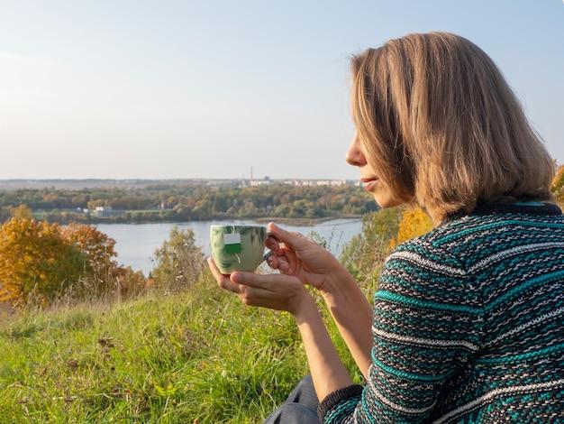 Le mani delle donne tengono una tazza di porcellana con un sacchetto all'interno, bevono tè verde caldo alla natura. la donna gode della bevanda calda o della bevanda in tazza, si rilassa il resto avendo pausa fuori.
