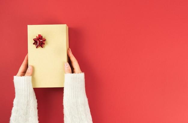 Mani delle donne che tengono scatola regalo chiusa con ornamento su sfondo rosso. giorno di san valentino