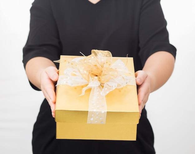 Mani delle donne che tengono il contenitore di regalo dell'oro. donne che fanno attenzione al vestito nero su fondo bianco