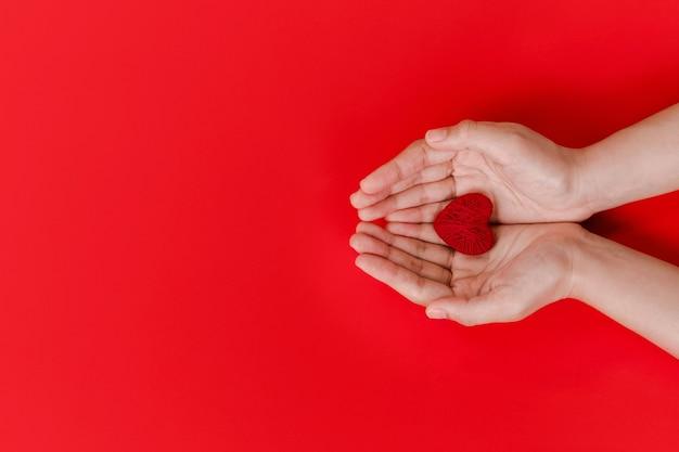 Mani delle donne che tengono cuore rosso sul rosso