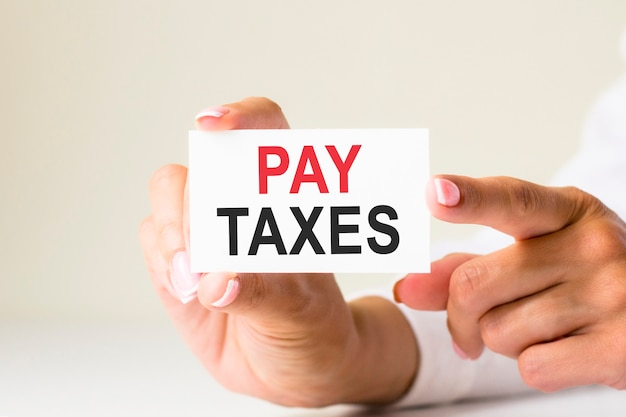 Le mani delle donne tengono un pezzo di carta bianca con il testo: paga le tasse. sfondo giallo. può essere utilizzato per affari, marketing, concetto finanziario
