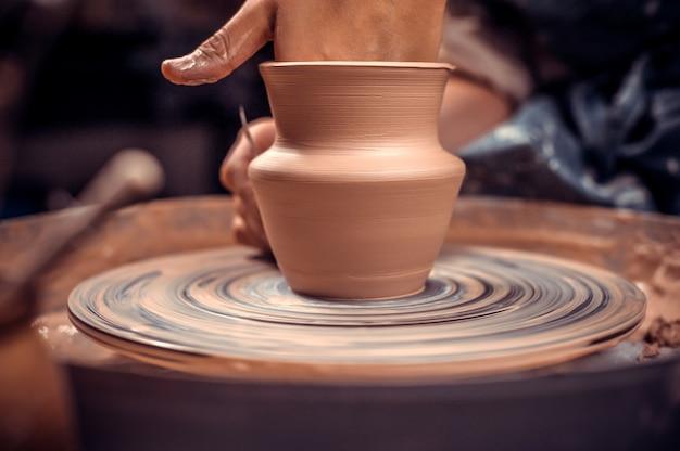 Mani delle donne. potter al lavoro. creare piatti. tornio da vasaio. mani sporche nell'argilla e tornio da vasaio con il prodotto. creazione. vasaio di lavoro.