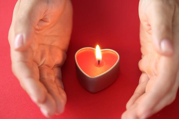 Le mani delle donne proteggono il fuoco ardente nella candela sotto forma di amore eterno del cuore e concetto di sentimenti